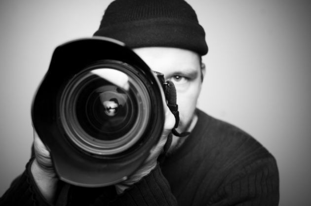 It is a black and white photo of a person who is holding a camera in his hand.