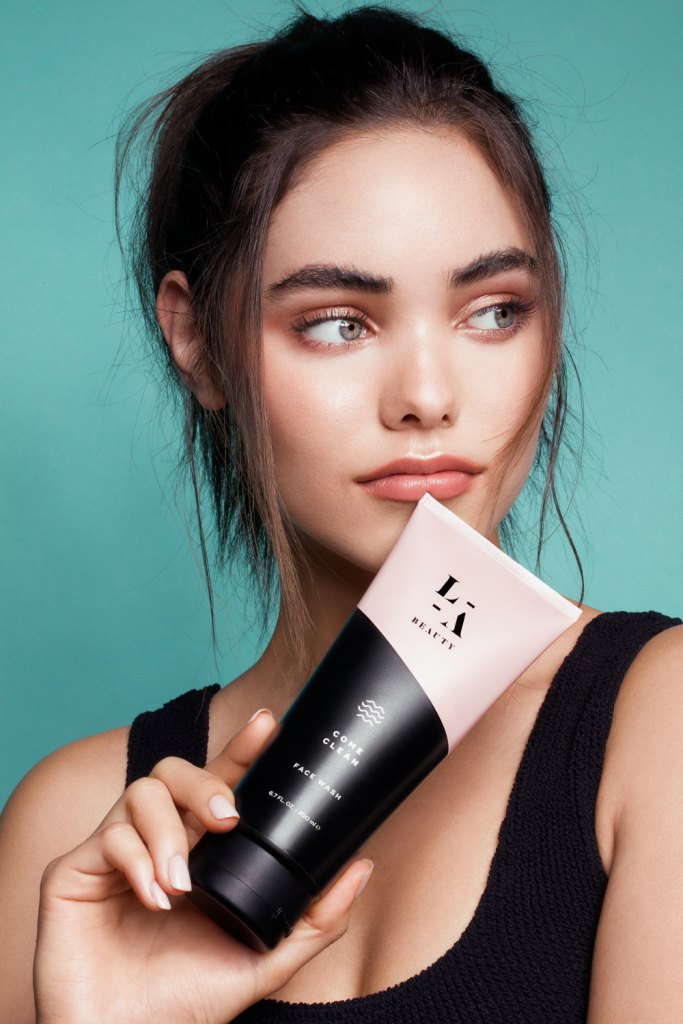 A portrait of a women endorsing a beauty product in her right hand while facing towards her left side.