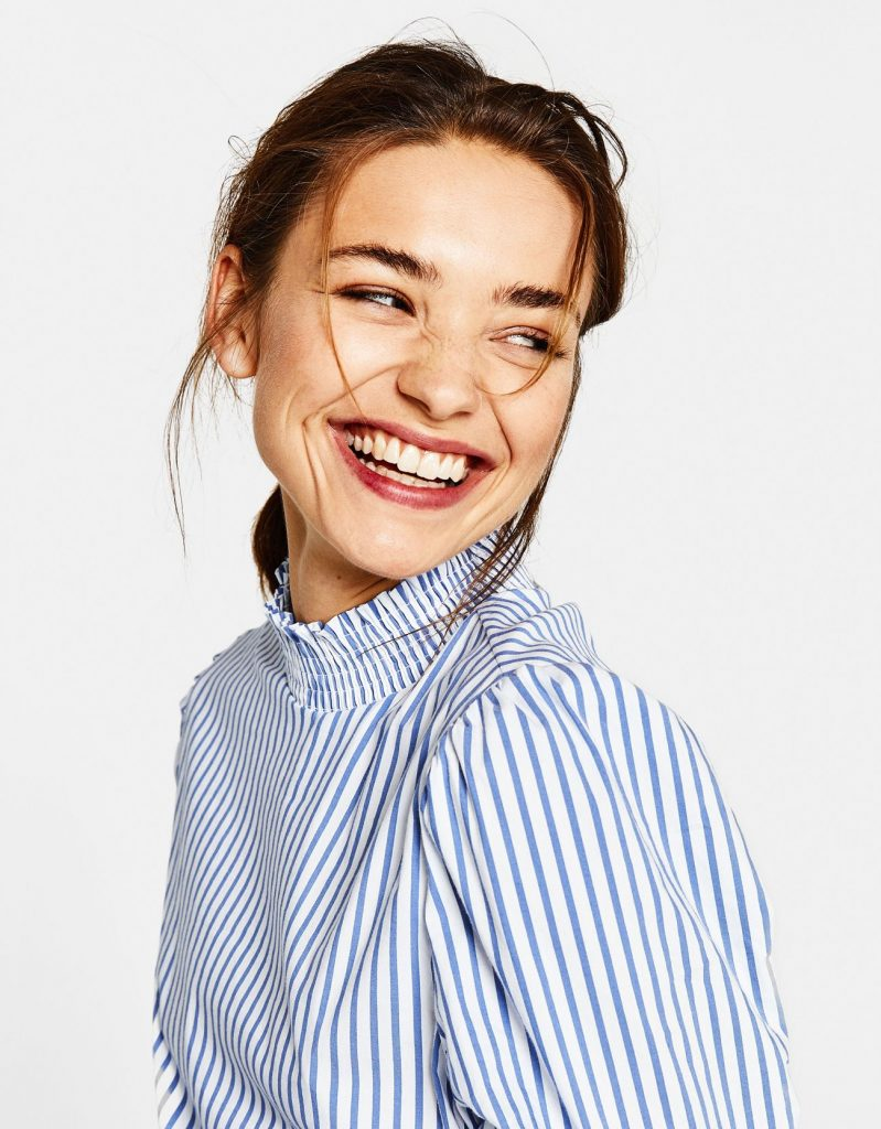 A portrait of a women wearing a blue and white striped top and smiling with teeth with posing.
