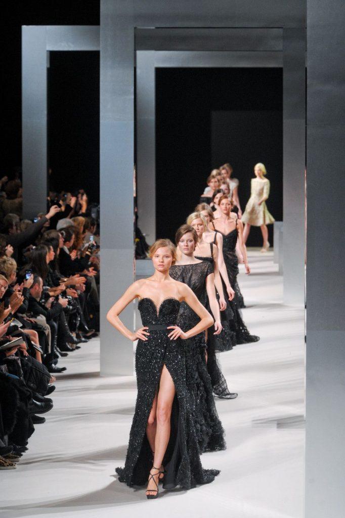 Models walking in a runway wearing black gowns.