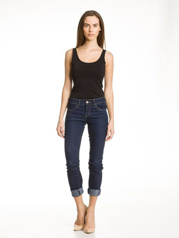 Portrait of a women wearing a black vest top and a blue jeans with a pair of skin colour stillettos.