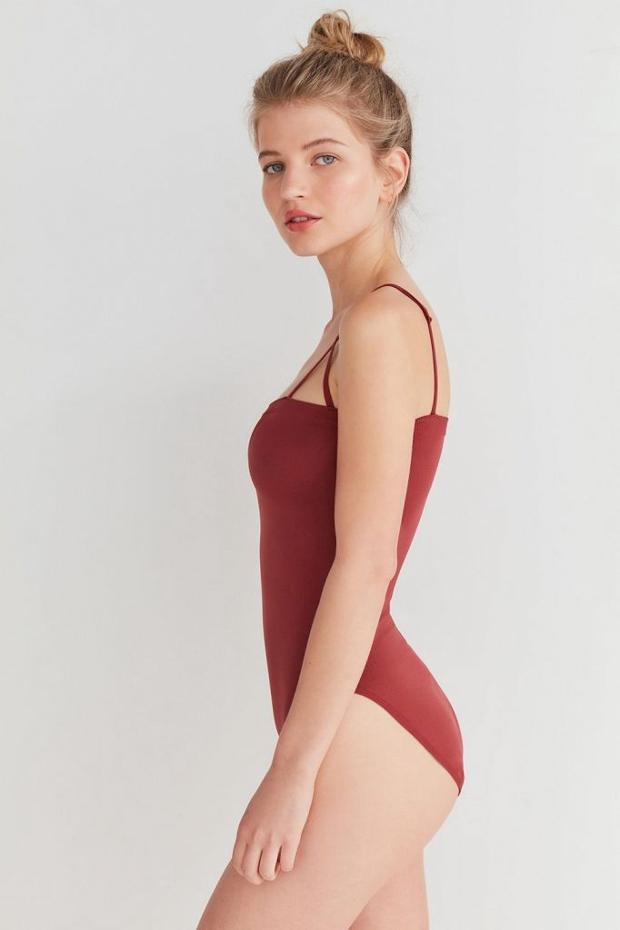 Portrait of a model in a rust coloured swimsuit and posing in her left profile.