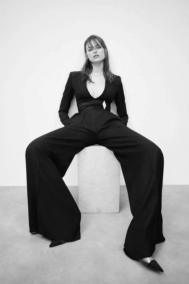 A Portrait of a women wearing black pants and top and sitting at a box while posing.