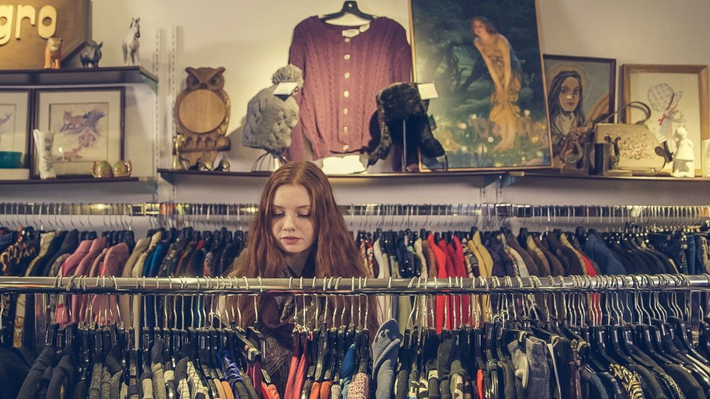 A girls is deciding her clothes in the wardrobe.