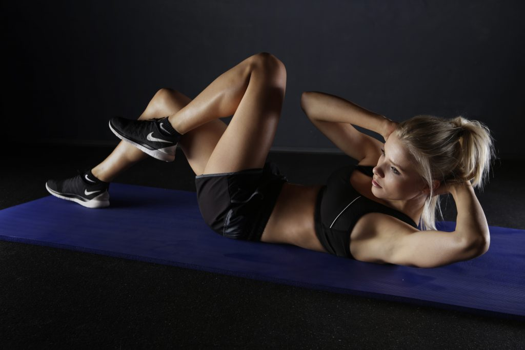 A women doing exercise in the floor.